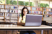 Smiling female student working with laptop in a high school libr — Stock Photo