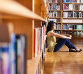 Thoughtful pretty girl sitting at college library — Stock Photo