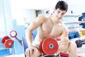 Smiling handsome man lifting heavy free weights at the gym — Stock Photo