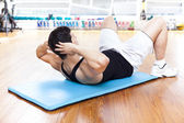 Handsome man exercising abdominal muscles at the gym — 图库照片