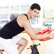 图库照片: Handsome young man doing sport Spinning in the gym for fitness