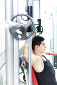 Handsome young man lifting heavy weights at the gym — Stock Photo