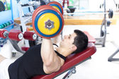 Strong man lifting heavy free weights at the gym — Stock Photo