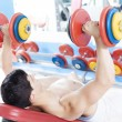 Shirtless young mlifting heavy free weights at gym — Stock Photo #30368595