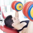 Stock Photo: Young handsome mlifting heavy free weights at gym
