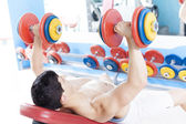 Shirtless young man lifting heavy free weights at the gym — Stock Photo