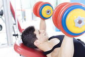 Young handsome man lifting heavy free weights at the gym — Stock Photo
