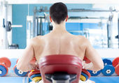 Handsome man from back training with weights at the gym — Stock Photo