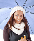 Beautiful young girl with blue umbrella and winter clothing — Stock Photo