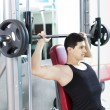 Handsome man lifting heavy weights at the gym — Stock Photo