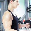 Handsome man lifting heavy free weights at the gym — Stock Photo