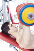 Strong handsome man lifting heavy free weights at the gym — Stock Photo