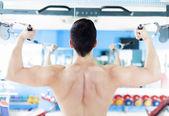 Stark stilig man utövar sin rygg på gymmet — Stockfoto
