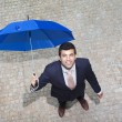 Handsome businessman looking to the sky and checking if it's raining — Foto Stock