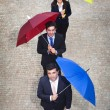 Business people holding colorful umbrellas outdoors — Stok fotoğraf