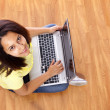 Beautiful woman sitting on the floor and working with a laptop at home — Stock Photo
