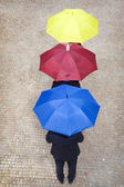 Business people hidden under colorful umbrellas, lined up — Stock Photo