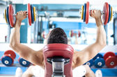 Stong man lifting weights in the gym — Stock Photo