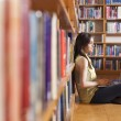 Young smiling student using her laptop in a library — Stock Photo