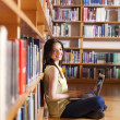 Young smiling student using her laptop in a library — Stock Photo #33750869
