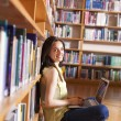 Young smiling student using her laptop in a library — Stock Photo #33750907
