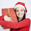 Happy Santa girl holding a gift — Stock Photo