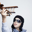 Happy kid playing with toy airplane against gray background — Stock Photo #39301075