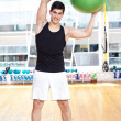 Young athletic man exercising workout fitness ball at the gym — Stock Photo