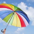 Rainbow umbrella in woman hands against cloudy sky — Stock Photo
