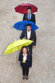 Business people holding colorful umbrellas — Stock Photo