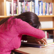 Tired student girl sleeping on the table at the library — Stock Photo #48084029