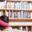 Tired student girl sleeping on the table at the library — Stock Photo