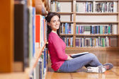 Portrait of a smiling young student reading a book in a library — Stock Photo