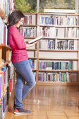 Student reading book in library — Stock Photo