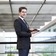 Smiling young businessman using his digital tablet at the office — Stock Photo #49612487