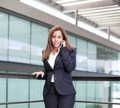 Leende ung affärskvinna talar i mobiltelefon på kontoret — Stockfoto