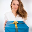 Beautiful young woman with a gift standing inside shopping — Stock Photo #9359671