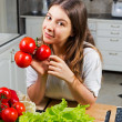 Young woman with tomato standing at kitchen — Stock Photo