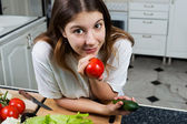 Young woman with tomato looking at camera — Stock Photo