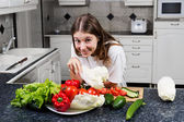 Young female cook making a fresh salad with organic vegetables — Stock Photo
