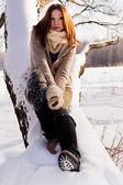 Cute blond sitting in a winter park, sunny day. — Stock fotografie