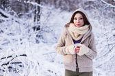 Cute woman in snowy forest, wearing fur coat — Stock Photo