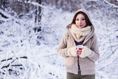 Cute woman in snowy forest, wearing fur coat — Stockfoto