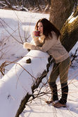Beautiful young woman drinking hot tea in winter forest. — Stock Photo