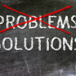 Problem and Solutions option handwritten with white chalk on a blackboard. — Stock Photo #19112531