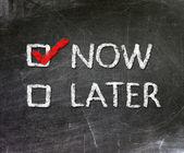 Now and Later option handwritten with white chalk on a blackboard. — Stock Photo
