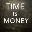 Time is money handwritten with white chalk on a dark background — Stock Photo #19219331