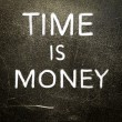 Time is money handwritten with white chalk on a dark background - Stock Photo