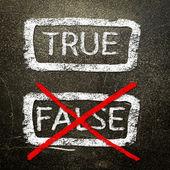 Sant eller falskt skriven på en svart tavla med vit krita. — Stockfoto