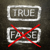 True or false written on a blackboard with white chalk. — Stockfoto